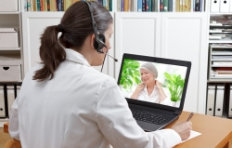 doctor sitting at the desk of her office with headset and laptop
