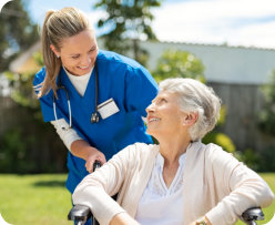 caregiver smiling with senior woman on wheelchair