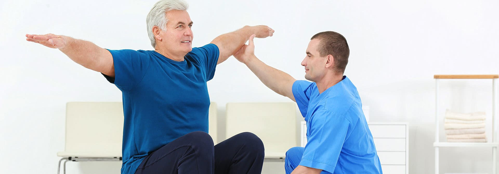 senior man doing exercise with his caregiver