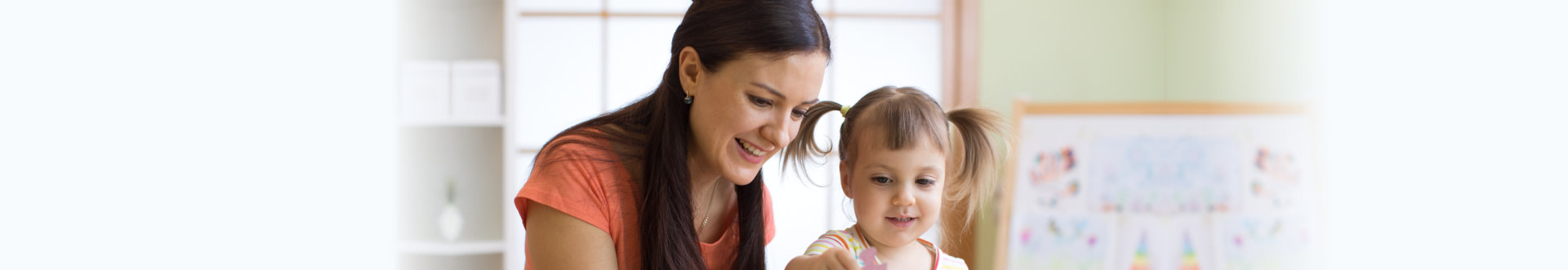 caregiver guiding the child to solve the puzzle