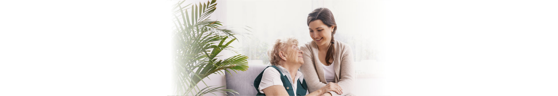 caregiver and elder in wheelchair smilling each other