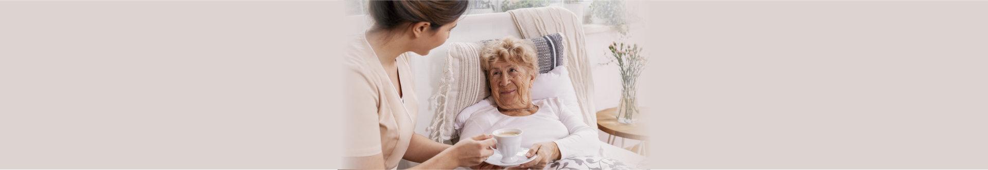 caregiver giving a blanket to an elder