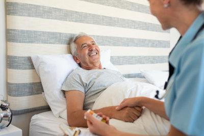 portrait of senior man and caregiver shaking hands