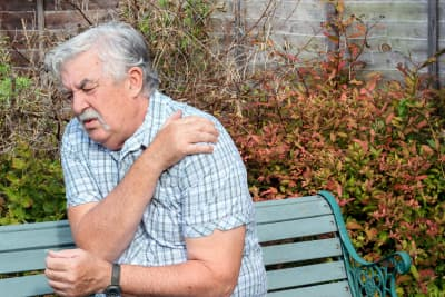 An elderly man holding his shoulder because of pain