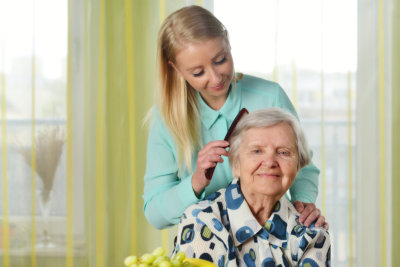 caregiver giving hygiene assistance to senior woman